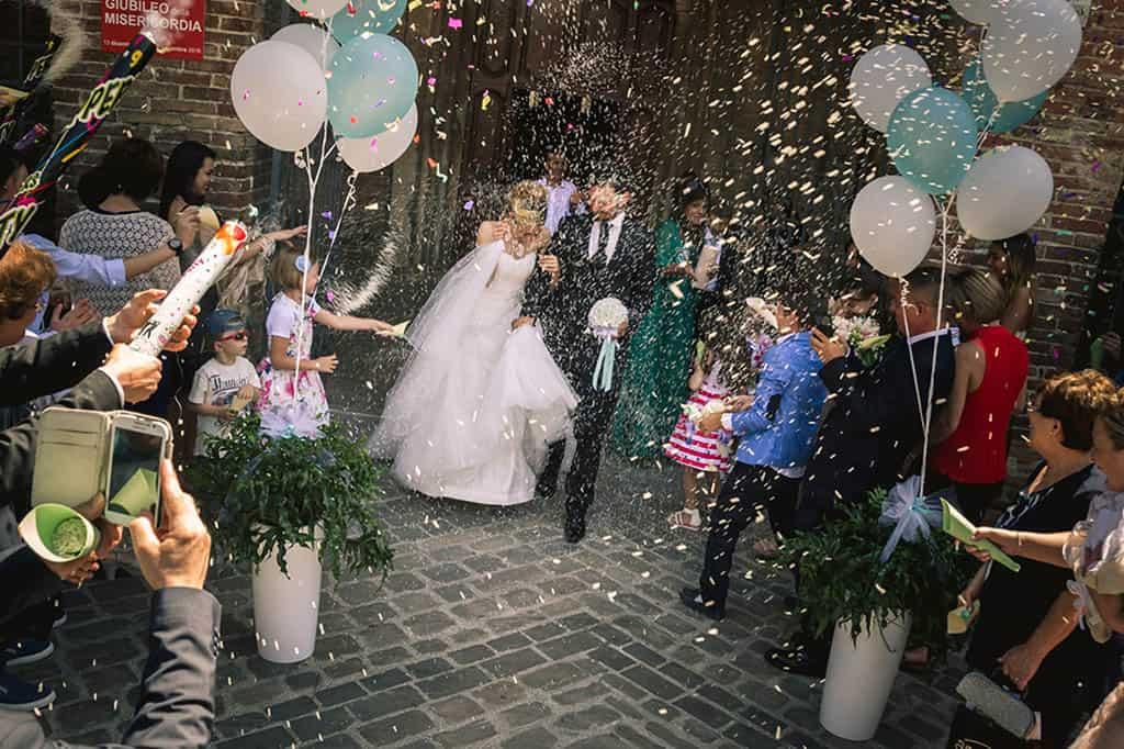 Foto sposi all'uscita della chiesa con lancio del riso e palloncini colorati