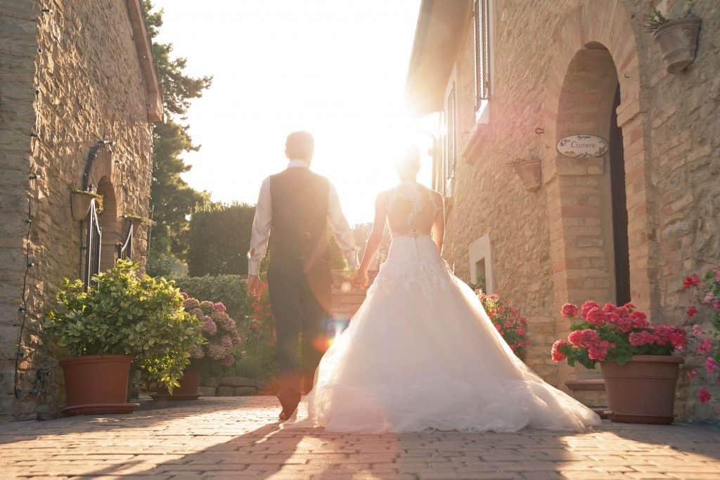Sposi che uscendo dalla villa camminano verso il sole
