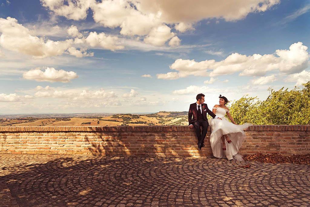 Sposi seduti su un muretto nelle vivinanze di jesi con veduta panoramica