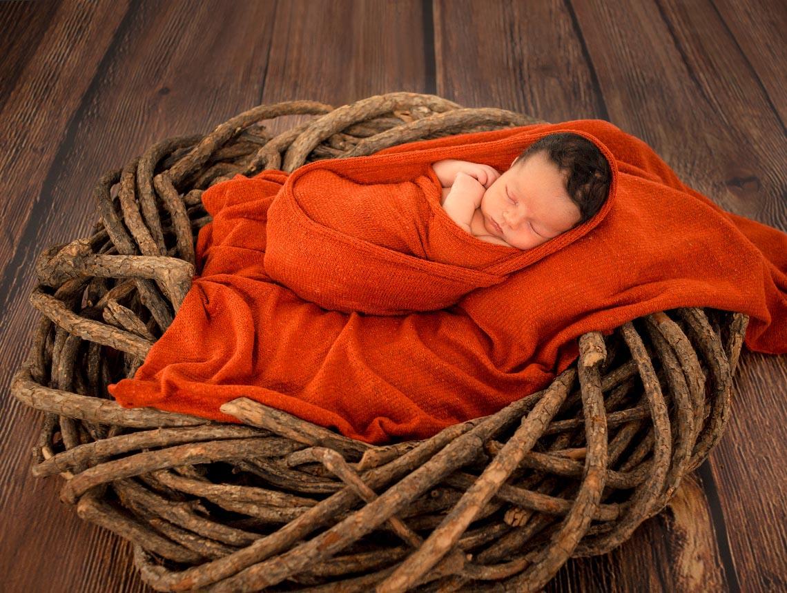 Foto neonato avvolto da tessuti arancioni sopra un fascio di rami di legno con sfondo listoni marrone