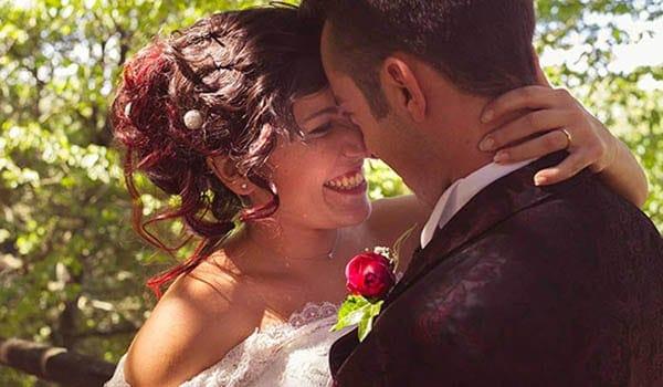 sposi al parco abbracciati e sorridenti illuminati da un raggio di sole