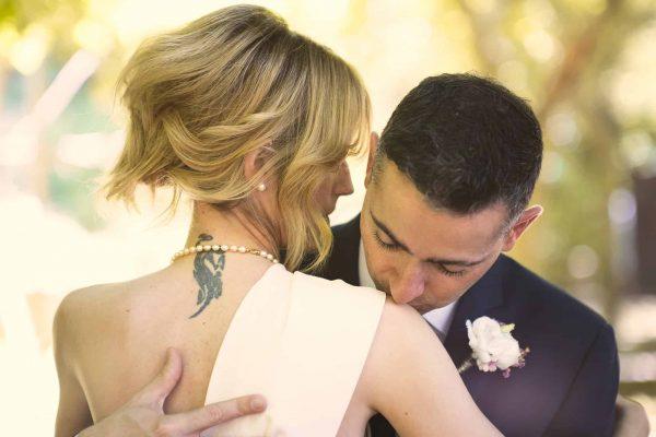 Sposo che bacia la sposa sulla spalla